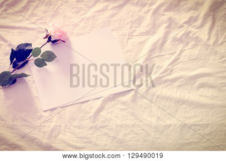 Vintage color style effect : Blank / empty papers with artificial pink rose on a crumpled bed sheet / unmade bed. Blank space for leaving an emotional message to someone special i.e. girlfriend wife