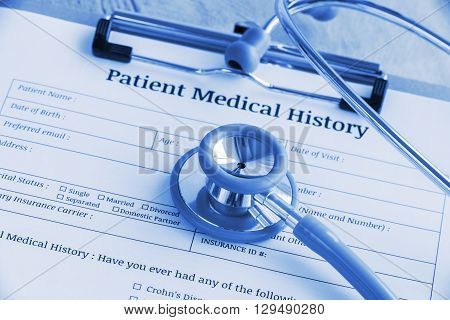 Patient medical history on a clipboard with stethoscope and a blue ballpoint pen putting on a physician's table. Blank form waiting to be filled and reviewed / examined by nurse / clinical assistant.