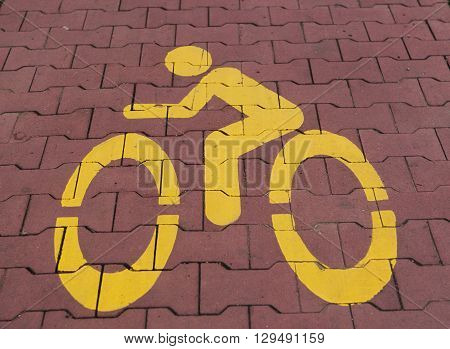 A bike lane or bike way symbol on asphalt roadway.