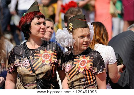 Orel Russia - May 9 2016: Celebration of 71th anniversary of the Victory Day (WWII). Woman and girl with field caps and st.George ribbons closeup