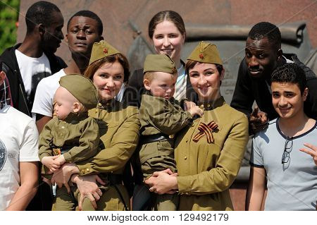 Orel Russia - May 9 2016: Celebration of 71th anniversary of the Victory Day (WWII). Russian women and children in military uniform with African and Indian men horizontal