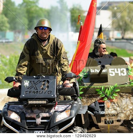 Orel Russia - May 9 2016: Celebration of 71th anniversary of the Victory Day (WWII). Men in uniform driving military machines with red flags closeup