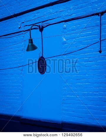 Deep blue brick wall with a closed up window, light, conduit and wires.