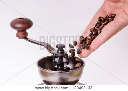 Manual coffee grinder with coffee beans. Isolated. White background. Modern style. Roasted coffee beans. Man hand and falling coffee beans.