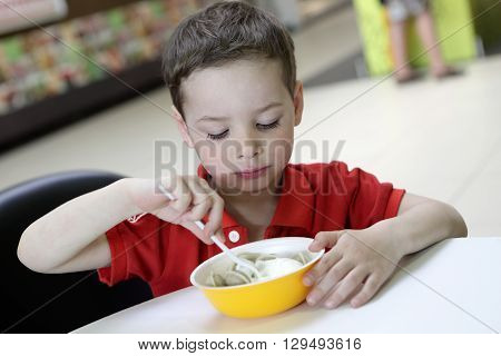 Child eating meat dumplings with sour cream in cafe