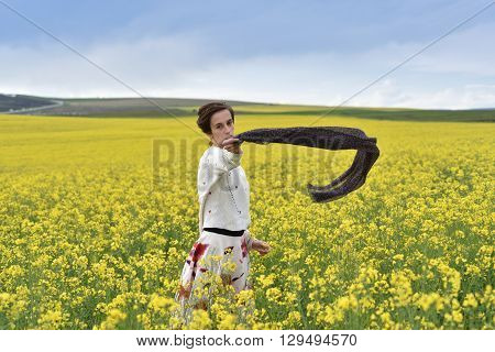 Brunette Young Woman Playing With Scarf In A Canola Field