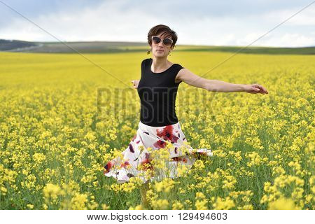 Hipster Girl Walking Through A Canola Field. Freedom Concept