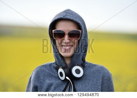 Hipster Girl In Hoodie, Sunglasses And Headphones In The Outdoors