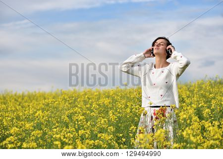 Young, Emotional And Happy Woman Listening Music In Headphones In A Canola Field