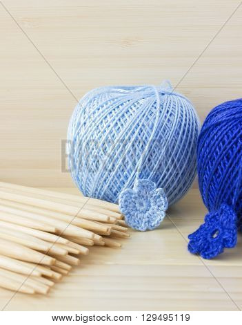Blue balls of cotton yarn for knitting crochet. Wooden needles bamboo background