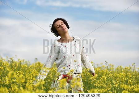 Sensual Lady Listening Music In Headphones And Dancing In A Canola Field