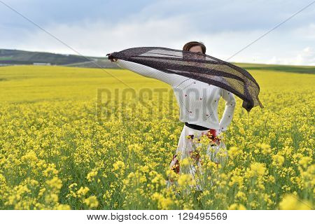 Young Woman Playing With Scarf In A Canola Field