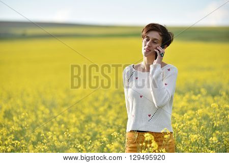 Young Woman Talking On Her Smart Phone In The Middle Of A Canola Field