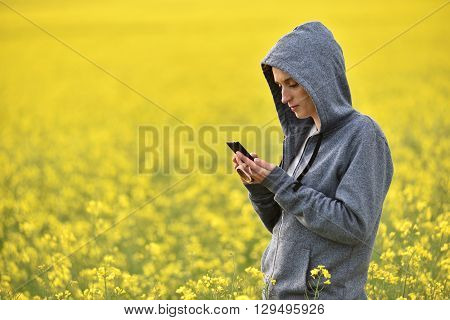 Young Woman In Hoodie Texting A Message On Her Smart Phone