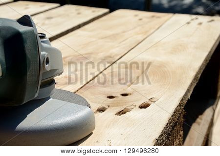 Front part of angle grinder with abrasive disc on planks after work.