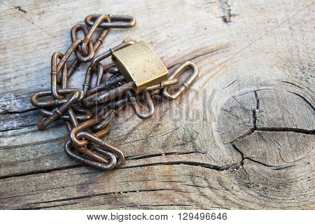 Rusty old chain and padlock on a grey wooden table background