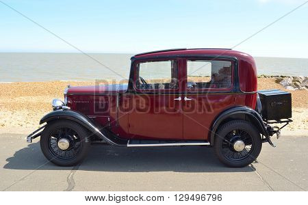 Felixstowe, Suffolk, England - May 01, 2016: Vintage dark red Austin Motor car parked on seafront promenade.