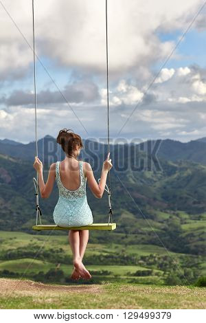 A woman dreaming on a swing and watching a beautiful mountain ridge