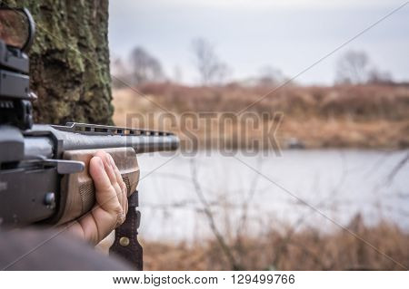 Hand holding shotgun aiming and ready to shot during hunting with copy space