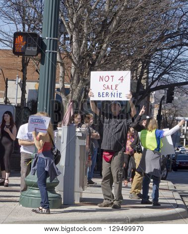 Ashevillem North Carolinam USA - February 28m 2016: Crowd of Bernie Sanders supporters stand on a street corner holding signs and interacting with cars and passersby during a political rally on February 28 2016 in downtown Ashevillem NC