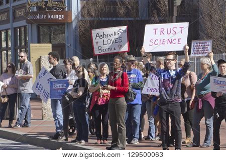 Asheville, North Carolina, USA - February 28, 2016: Crowd of Bernie Sanders supporters stand on a street corner holding signs and interacting with cars and passersby during a political rally on February 28 2016 in downtown Asheville, NC