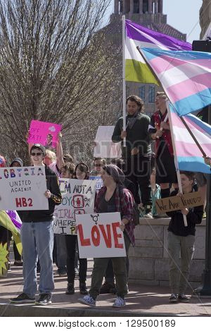 Asheville, North Carolina, USA - April 2, 2016: Crowd holds signs waves symbolic flags to protest the new North Carolina HB2 Law that restricts the rights of those who are gay or transgender on April 2, 2016 in downtown Asheville, NC