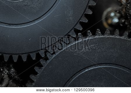 Two interlocked dirty gearwheels in the action