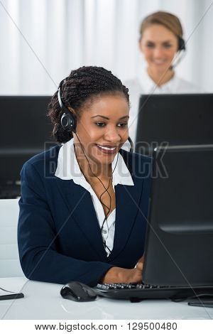 Happy Female Employee With Headset Working On Computer At Desk
