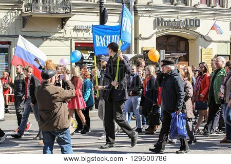 St. Petersburg, Russia - 1 May, A tall young man carrying a placard, 1 May, 2016. Day festive demonstration on the Nevsky Prospect in St. Petersburg, the first of May.