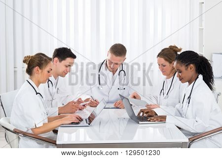 Group Of Doctors Using Digital Tablet And Laptop At The Meeting In Hospital