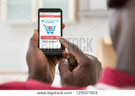 Close-up Of A African Man Shopping Online Using Mobile Phone