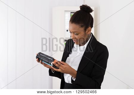 Young African Businesswoman Looking At Cartridge In Office