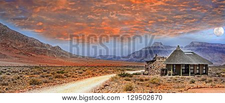 African Lodge in the Namib Desert with mountains and cloudy red sunset and moon