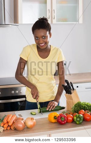 Young Happy Woman Chopping Vegetables On Chopping Board