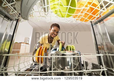 Young Happy African Woman Removing Plate From The Dishwasher