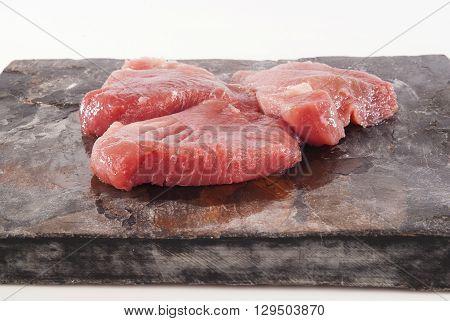 Fresh raw tuna steaks against grey slate