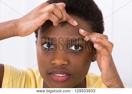 Close-up Of Young African Woman Looking At Pimple On Forehead