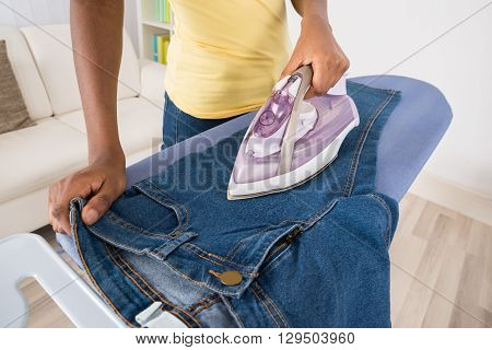 Close-up Of Woman Ironing Jeans On Ironing Board At Home