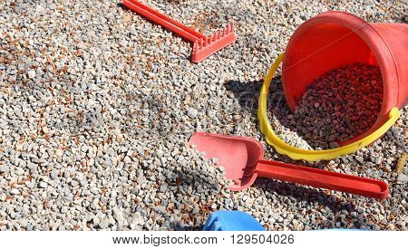 Rake Shovel And Bucket Child On Playground Gravel