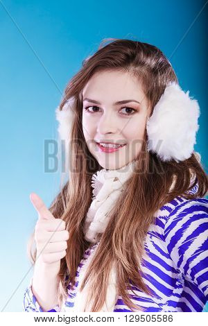 Smiling teenage girl wearing fluffy white earmuff in winter fashion. Giving thumbs up sign.