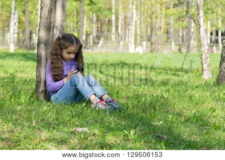 Cute little long-haired girl sitting on the grass in a park with a mobile phone in her hands and sending message on phone mobile