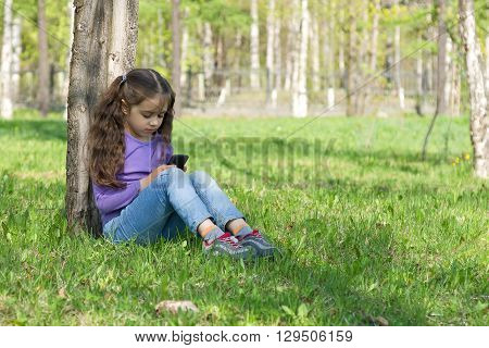 Cute little long-haired girl sitting on the grass in a park with a mobile phone in her hands and using modern smartphone