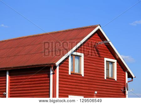 Wooden cottage of red - brown color on the background of sky