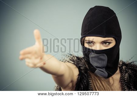 Woman in black balaclava making gun gesture. Crime and violence on blue studio shot