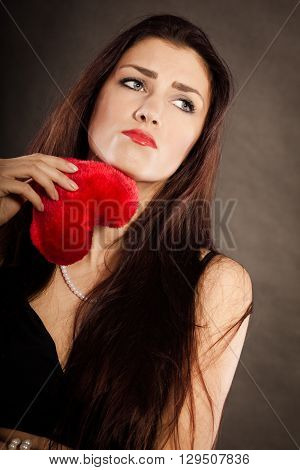 Woman brunette long hair girl wearing black dress holding red heart love symbol studio shot on dark. Heartbroken young female. Sad unhappy face expression