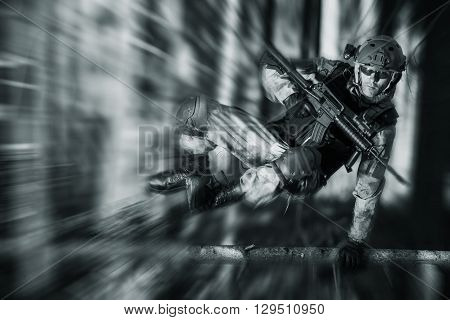 Army Soldier in Action Jumping Over Fallen Tree. Military Concept.