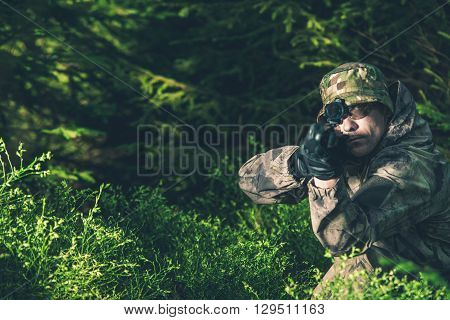 Forest Hunter. Poacher with Rifle Spotting Some Deers.