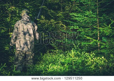 Illegal Hunting Poacher in the Forest. Poacher with Rifle.