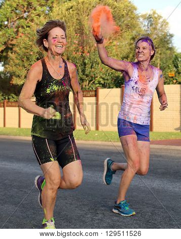 Rustenburg Marathon Club Rainbow Run - NOVEMBER 25: Young lady plashing other with orange powder paint at colour run on November 25 2015 Rustenburg South Africa.