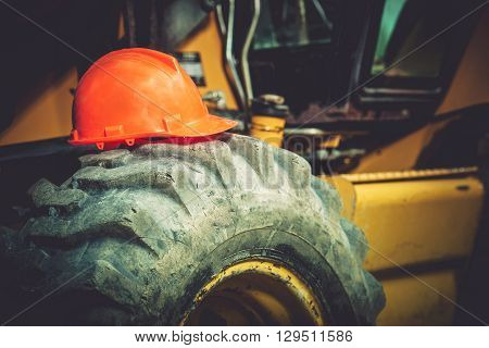 Work Safety Concept. Safety While Construction Working. Orange Safety Construction Helmet on Large Heavy Duty Tractor Tire.